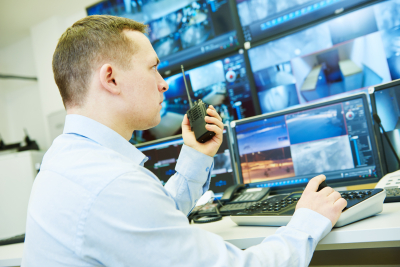 man holding a communicator device front of monitors